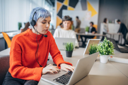 Woman with headset on laptop